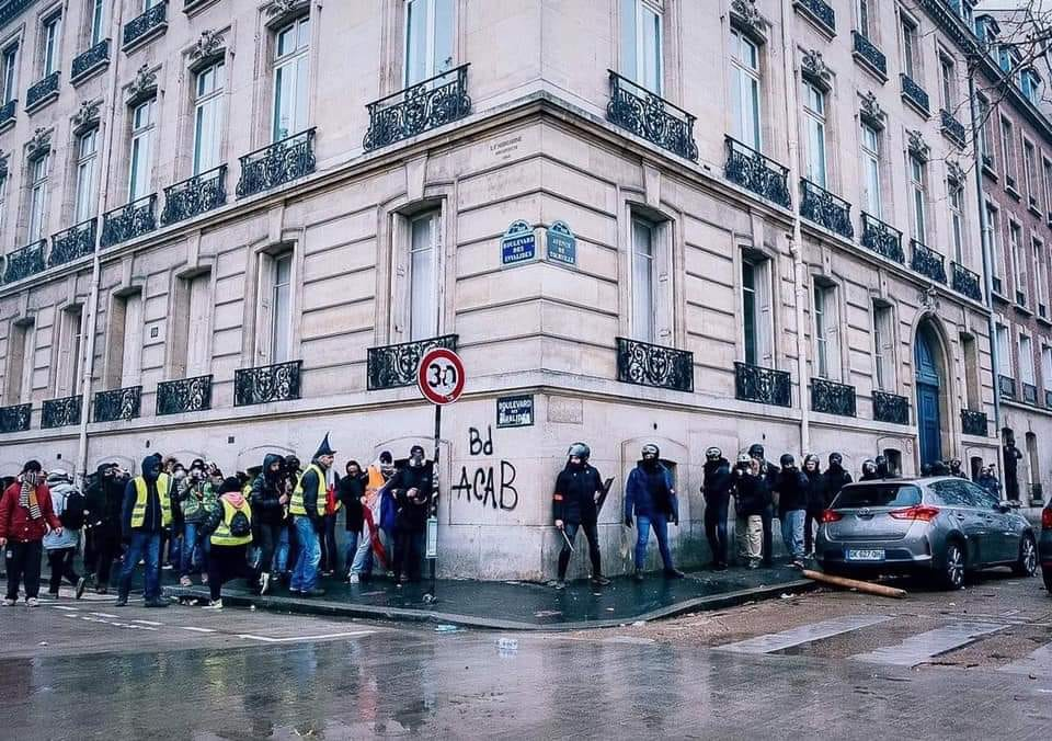 Yellow vests hiding behind one corner of the building and police hiding at the other.